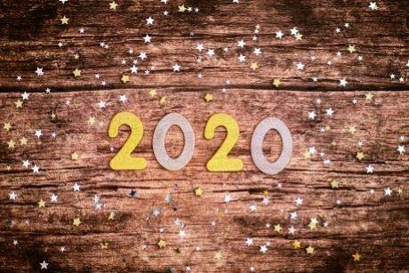 Photograph of the number 2020 with star confetti on a wooden background