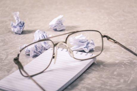 Pair of glasses on a pad of paper