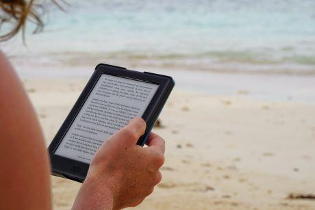 Person sitting on the beach reading from a tablet.