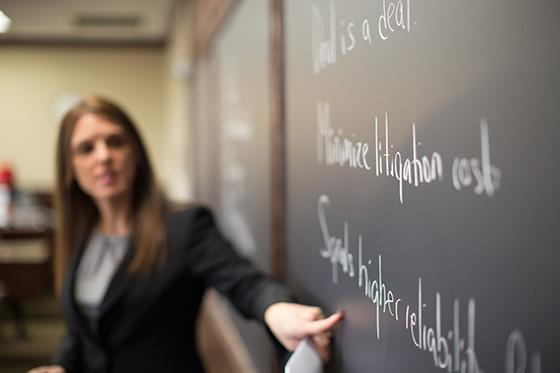 Professor points to notes on chalkboard